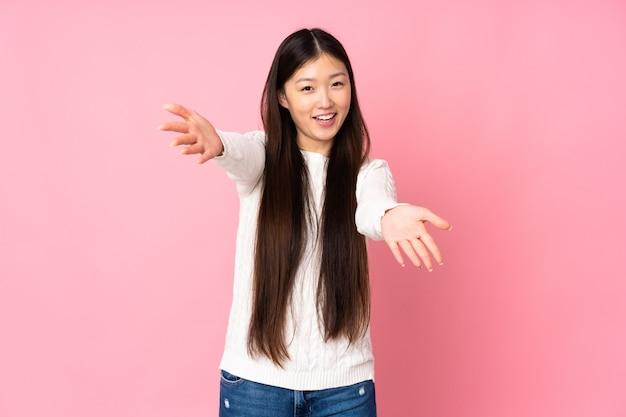若いアジアの女性は、手で来るために提示し、招待して孤立しました