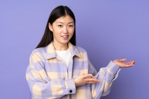 Young asian woman isolated on purple space extending hands to the side for inviting to come