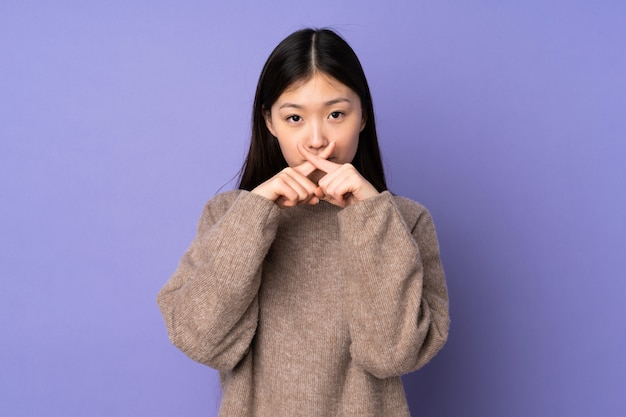 Young asian woman isolated on purple space showing a sign of silence gesture