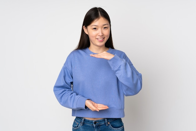 Young asian woman isolated on wall holding copyspace imaginary on the palm to insert an ad