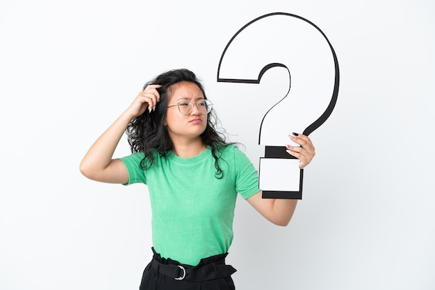 Young asian woman isolated on white background holding a question mark icon and having doubts