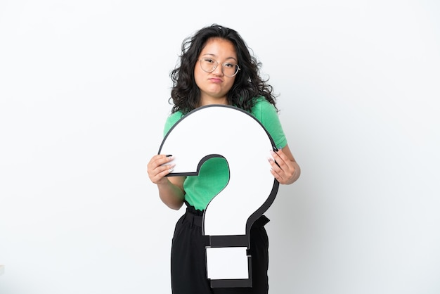 Young asian woman isolated on white background holding a question mark icon and with sad expression