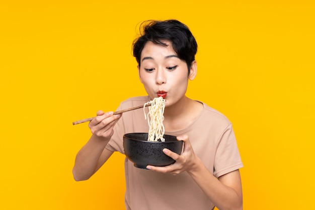Young asian woman over isolated yellow wall holding a bowl of noodles with chopstick sand blowing it because they are hot