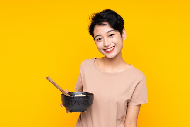 Young asian woman over isolated yellow wall smiling a lot while holding a bowl of noodles with chopsticks