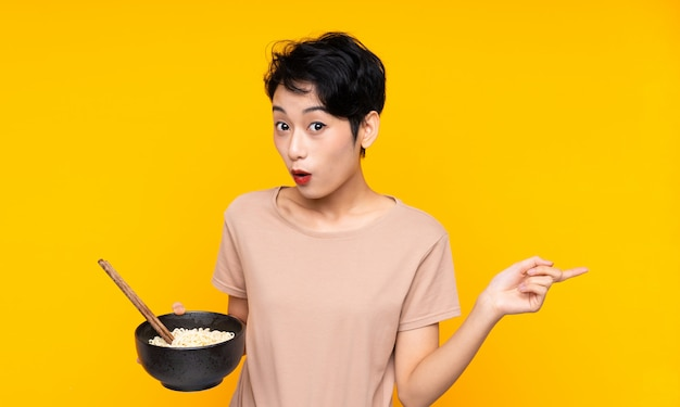 Young asian woman over isolated yellow wall surprised and pointing side while holding a bowl of noodles with chopsticks