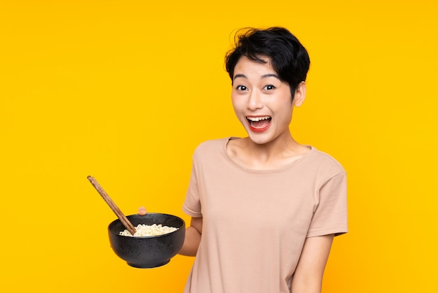 Young asian woman over isolated yellow wall with surprise and shocked facial expression while holding a bowl of noodles with chopsticks