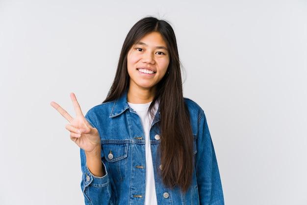 Молодая азиатская женщина радостная и беззаботная показывая символ мира с пальцами