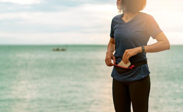 若いアジアの女性は、朝の海のビーチで有酸素運動を実行する前に、スマートフォンをウエストバッグに入れたままにします。屋外トレーニング。ランナーおよびスマートバンドウェアラブルデバイス。