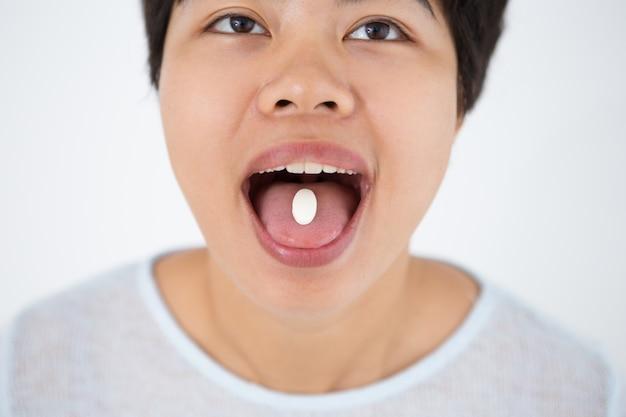 Молодая женщина азиатских держать таблетки на языке