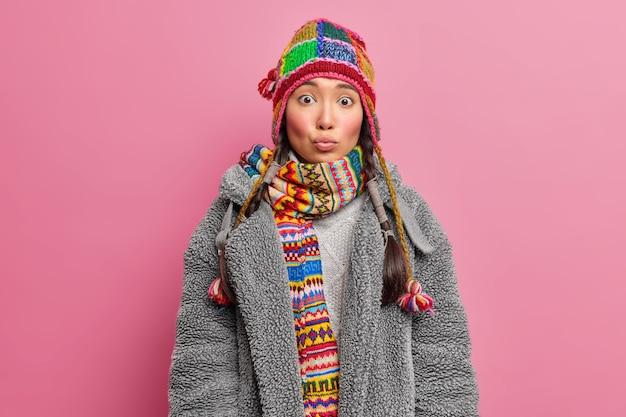 Молодая азиатская женщина держит губы округлыми, с удивленным выражением лица носит вязаную шапку и шарф, одетую в серую шубу, изолированную над розовой стеной