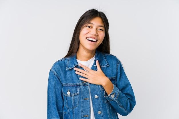 若いアジアの女性は胸に手を置いて大声で笑います。