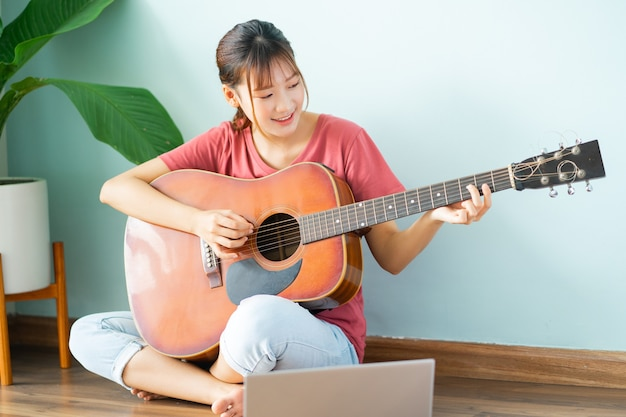 Young asian woman learning guitar at home