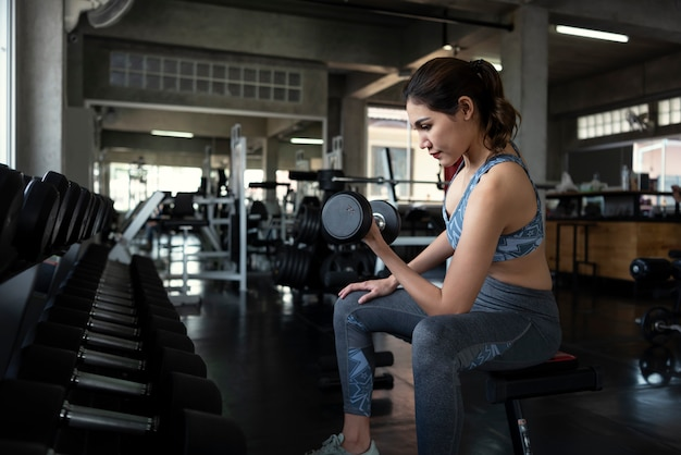 Young asian woman lifting dumbbells in gym fitness. healthy lifestyle and workout motivation concept.