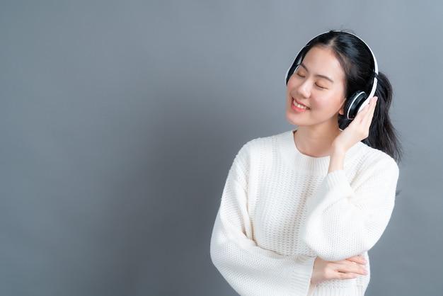 젊은 아시아 여자 듣기와 회색 벽에 헤드폰으로 음악을 즐길 수