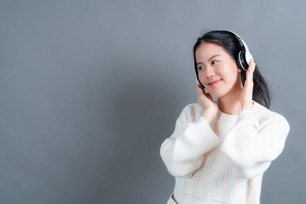 젊은 아시아 여자 듣고 회색 벽에 헤드폰으로 음악을 즐길 수
