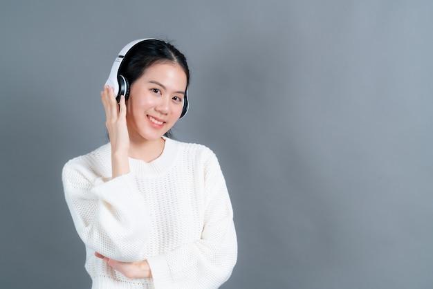 젊은 아시아 여성 듣기 및 헤드폰으로 음악을 즐길 수