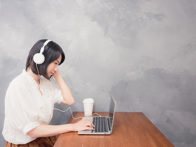 Young asian woman listening to headphones in front of laptop
