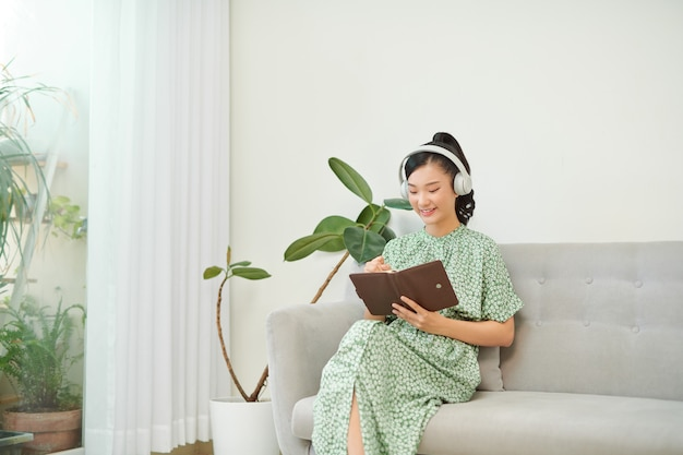 Young asian woman listening music from headphones and writing note for her work idea in diary book.