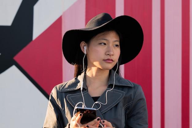 Молодая азиатская женщина слушает музыку со своего телефона