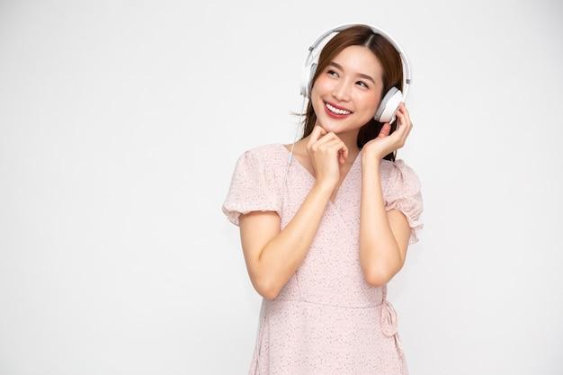고립 된 헤드폰으로 젊은 아시아 여성 듣는 음악