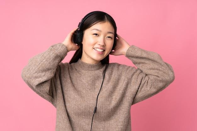 Молодая азиатская женщина слушает музыку