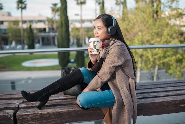コーヒーを飲みながら公園のベンチで黒いヘッドフォンで音楽を聴いている若いアジアの女性
