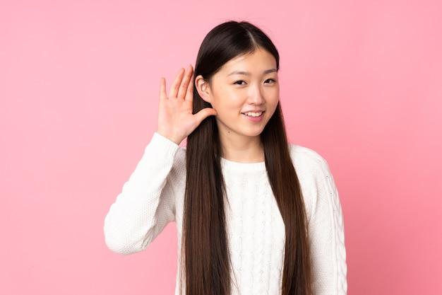 耳に手を置いて何かを聞いている若いアジアの女性