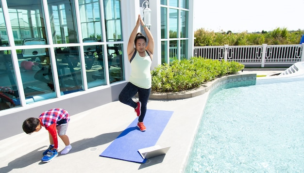 Young asian woman and little kid boy smiling while lying on yoga mat online training. healthy lifestyle and sport concepts.