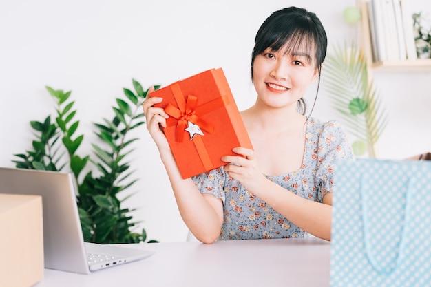 소셜 네트워킹 플랫폼에서 그녀의 스트림을 시청하는 청중에게 선물을주는 젊은 아시아 여성 라이브 스트림