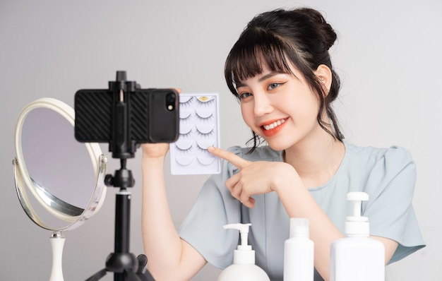 Young asian woman live streaming to teaching make up online