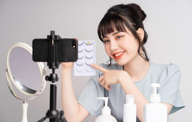Молодая азиатская женщина в прямом эфире учится макияжу онлайн