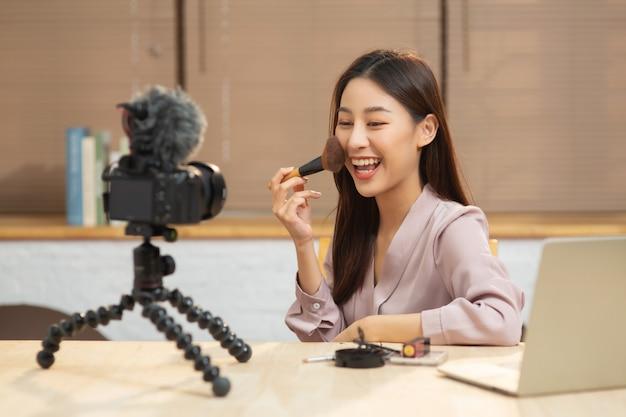 若いアジアの女性はオンライン化粧品の彼女の自己指導メイクを撮影するカメラの記録を見て