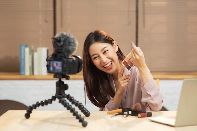 젊은 아시아 여성이 화장품 메이크업을 스스로 가르치는 카메라 기록을 보고 있다