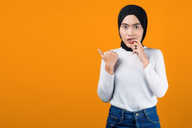 Young asian woman look confused and pointing to empty space