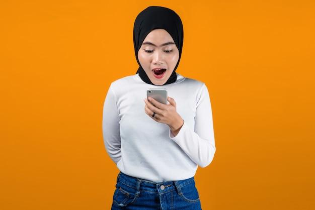 Молодая азиатская женщина выглядит потрясенной, используя мобильный телефон