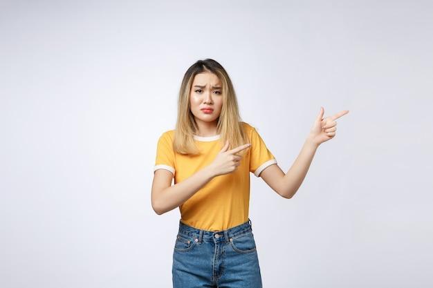 카메라에서 손가락을 가리키는 동안 화가 슬픈 찾고 젊은 아시아 여자