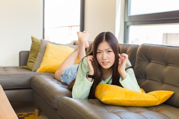 怒り、ストレス、イライラしているように見える若いアジアの女性は、耳をつんざくような音、音、または大音量の音楽で両耳を覆っています