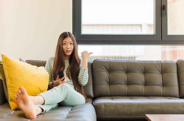 젊은 아시아 여자는 불신에 놀란 표정으로 옆에있는 물건을 가리키며 와우, 믿을 수 없다고 말하는
