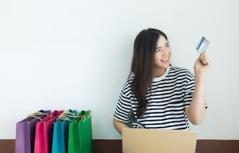 Молодая азиатская женщина смотря кредитную карточку с ее компьтер-книжкой и хозяйственными сумками. Интернет-магазин
