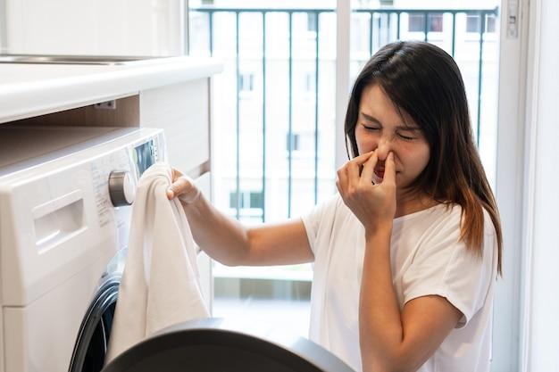 부엌에 있는 세탁기에서 더러운 냄새나는 옷을 보고 있는 젊은 아시아 여성.