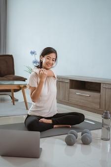 ノートパソコンを見て、自宅で自分で運動をしている若いアジアの女性