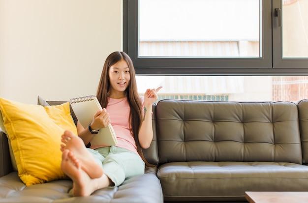 흥분 하 고 측면을 가리키는 놀 찾고 젊은 아시아 여자