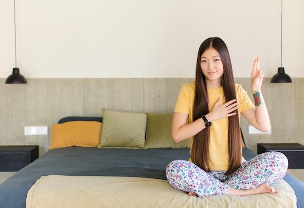 Молодая азиатская женщина выглядит счастливой, уверенной и заслуживающей доверия, улыбается и показывает знак победы, с позитивным настроем