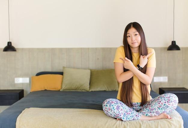 Молодая азиатская женщина выглядит счастливой, гордой и удивленной, весело указывая на себя, чувствуя себя уверенной и возвышенной Premium Фотографии