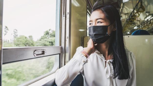 電車の中で座っている間、窓の外を見ている若いアジアの女性。