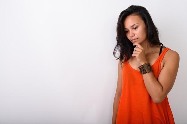 Молодая азиатская женщина выглядит грустно, думая против белого пространства