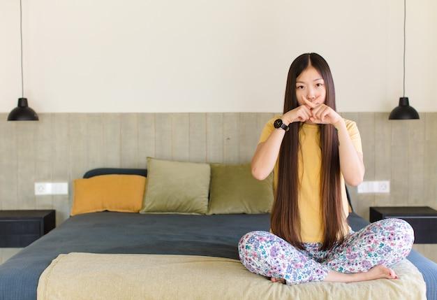 젊은 아시아 여자는 비밀을 유지, 침묵이나 조용을 요구하는 입술을 손가락으로 진지하고 십자가를 찾고