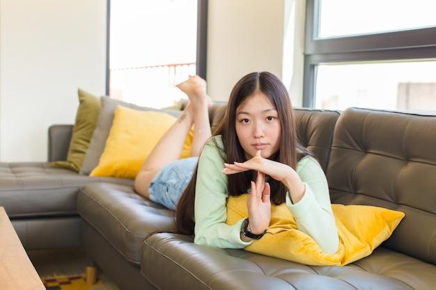 Молодая азиатская женщина выглядит серьезной, суровой, сердитой и недовольной, делая знак тайм-аута