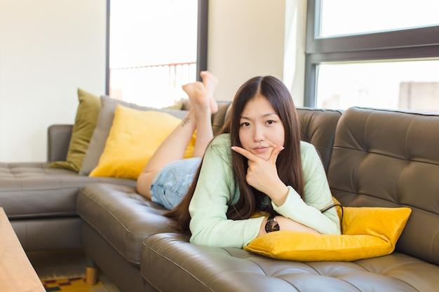 真面目で、思慮深く、不信感を抱き、片方の腕を組んで、あごに手を当て、オプションを重み付けする若いアジア人女性