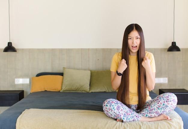 真面目で、不幸で、怒って、不機嫌そうに見える若いアジア人女性は、立ち入りを禁じているか、両手のひらを開いて停止すると言っています